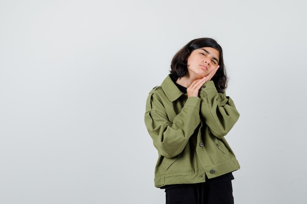 Cute teen girl leaning on palms as pillow in army green jacket and looking tired , front view.