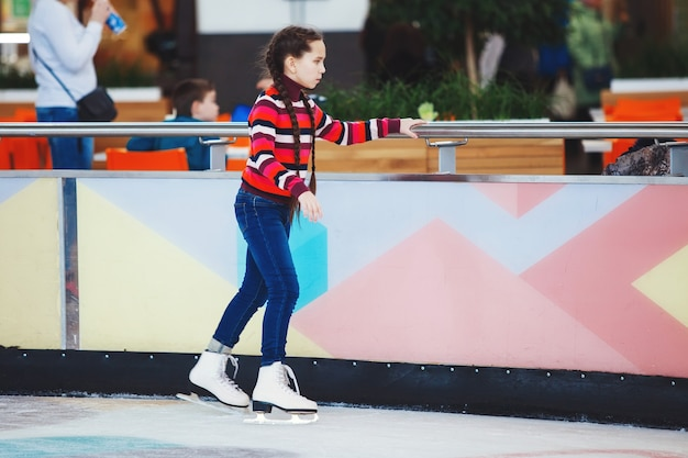 Cute teen girl learns to skate indoors on the ice in the mall