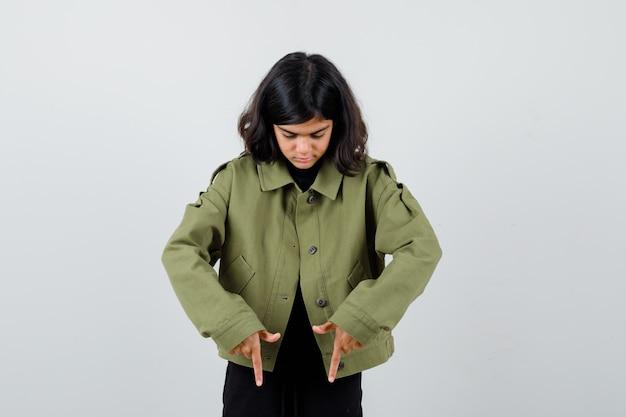 Ragazza teenager sveglia che indica giù in giacca verde dell'esercito e che sembra messa a fuoco. vista frontale.