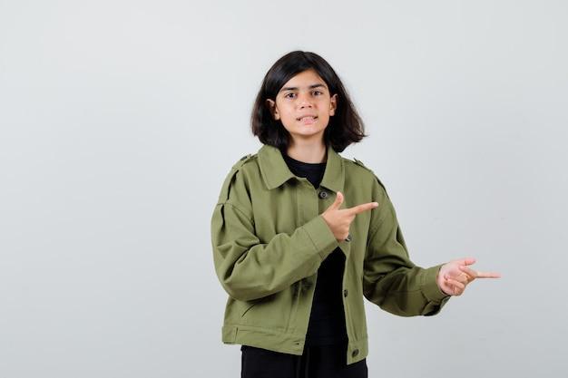 귀여운 십대 소녀가 군대 녹색 재킷을 똑바로 가리키고 쾌활한 앞모습을 보고 있습니다.