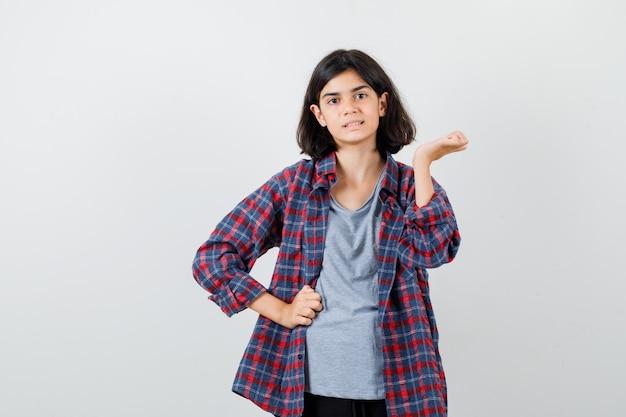 Ragazza teenager sveglia che finge di tenere qualcosa in camicia a quadri e sembra sicura. vista frontale.
