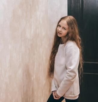 Симпатичная девочка-подросток с табличкой возле двери.