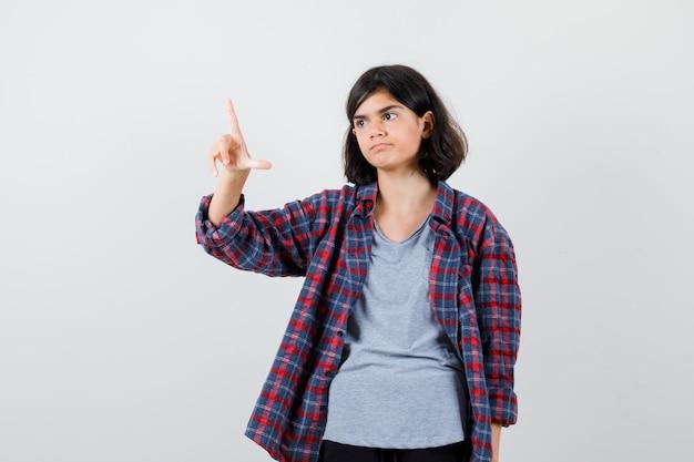 チェックシャツで目をそらし、元気のない、正面図を見ながら敗者のサインを示すかわいい十代の少女。