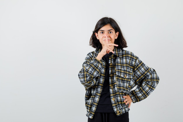 Милая девочка-подросток показывает жест молчания в клетчатой рубашке и смотрит осторожно. передний план.