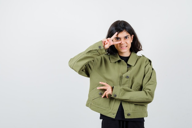 Cute teen girl showing v-sign on eye in army green jacket and looking cheerful , front view.