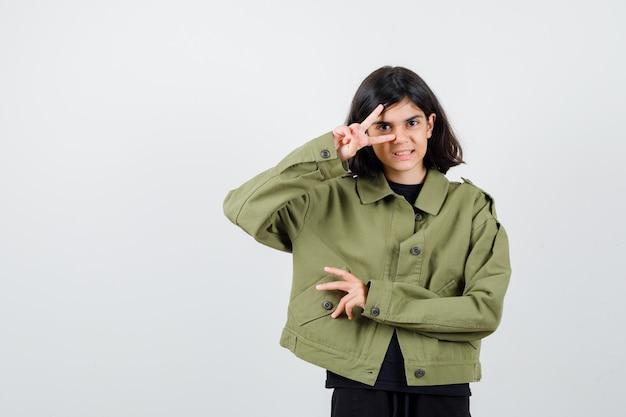 軍の緑のジャケットで目にvサインを示し、陽気に見える、正面図のかわいい十代の少女。