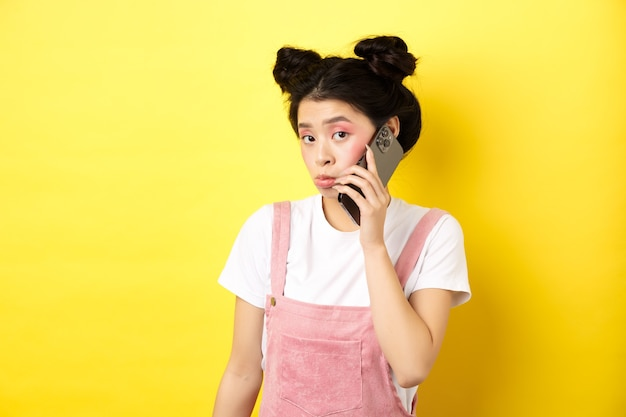 Cute teen girl talking on smartphone, making silly pouting face and look timid at camera, standing with glamour makeup on yellow background
