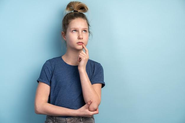 青い壁の壁に何かを考えているかわいい十代の少女