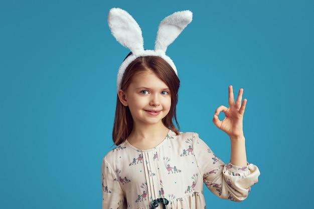 Симпатичная девочка-подросток с кроличьими ушками и повседневным платьем, показывающая знак