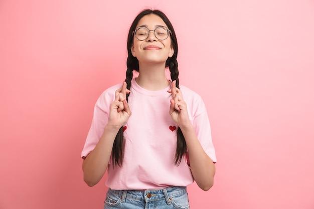 ピンクの壁に隔離された誓いのために笑顔と指を交差させたまま眼鏡をかけている2つの三つ編みのかわいい十代の少女