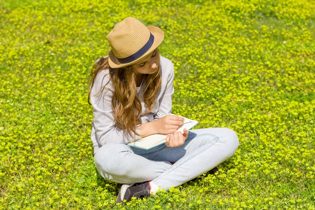 Cute teen girl writes notes on a paper pad on a green meadow.