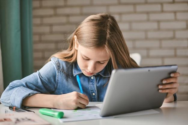 Симпатичный подросток школьница делает свою домашнюю работу с планшета на дому. ребенок пишет задание в тетради.