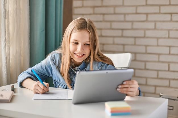 Симпатичный подросток школьница делает свою домашнюю работу с планшета на дому.