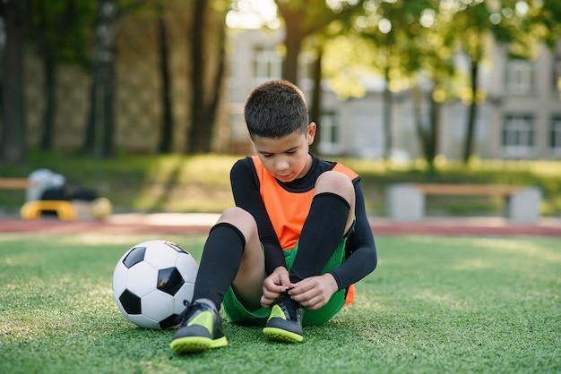 Милый подросток футболист на искусственном зеленом поле