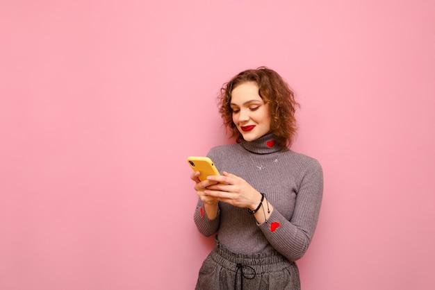곱슬 머리를 가진 귀여운 십대 여자는 스마트 폰에서 인터넷을 사용하고 있습니다