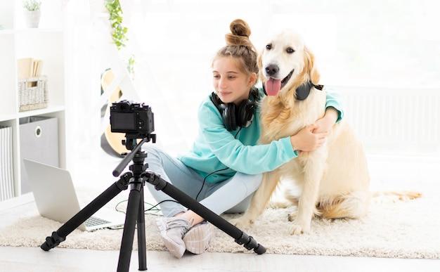 室内カメラの前で素敵な犬と一緒にかわいい 10 代のブロガーの女の子