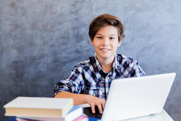 노트북에서 인터넷을 서핑하는 귀여운 십 대 소년