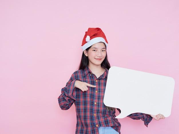 Милая девочка-подросток в шляпе санта, указывая пальцем на пустой плакат, стоя на розовом фоне.