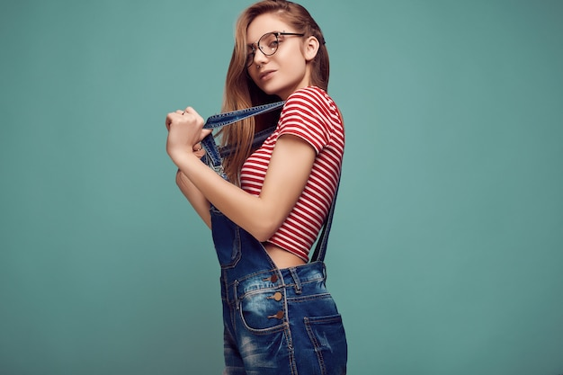 Cute teenage girl in denim overalls and glasses