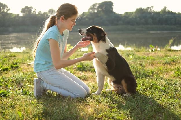 Симпатичная девочка-подросток обнимает щенка австралийской овчарки трех цветов летом. обучение. дай лапу. концепция ухода за домашними животными. любовь и дружба между человеком и животным.