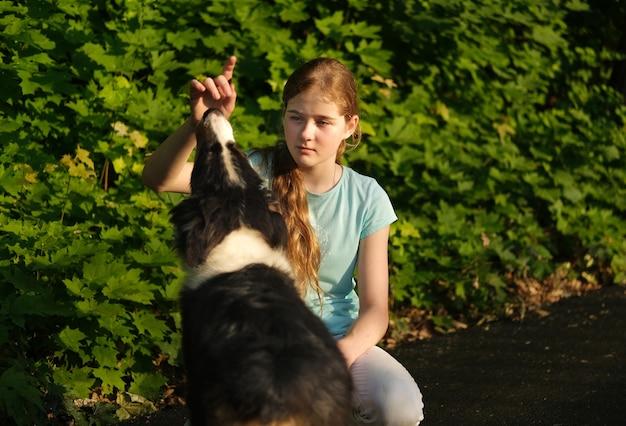 Симпатичная девочка-подросток обнимает щенка австралийской овчарки трех цветов летом. обучение. владелец. обработчик. концепция ухода за домашними животными. любовь и дружба между человеком и животным.
