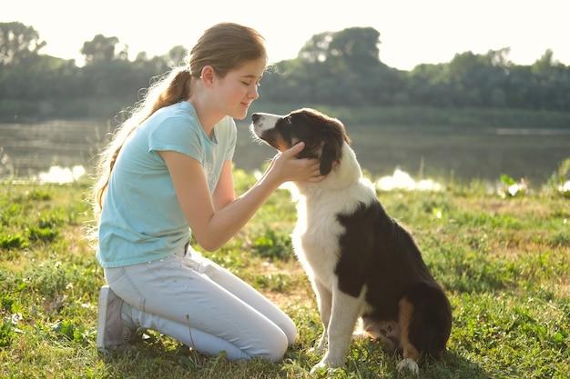 Симпатичная девочка-подросток обнимает трехцветного щенка австралийской овчарки летом