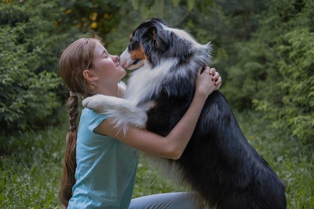Симпатичная девочка-подросток обнимает собаку австралийской овчарки трех цветов летом. концепция ухода за домашними животными. любовь и дружба между человеком и животным.