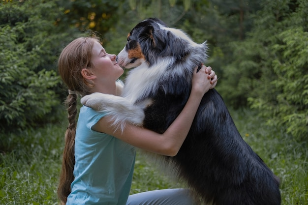 Cute teenage girl embrace hug australian shepherd three colours dog in summer. pets care concept. love and friendship between human and animal.