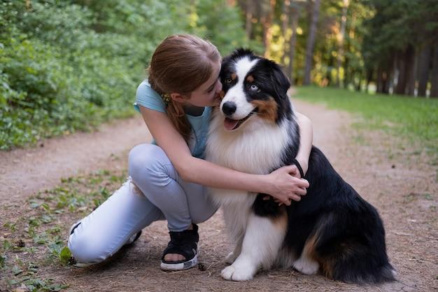Симпатичная девочка-подросток обнимает собаку австралийской овчарки трех цветов, целуя домашнее животное летом. концепция ухода за домашними животными. любовь и дружба между человеком и животным.