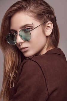 Cute teenage girl in fashion jacket and color glasses