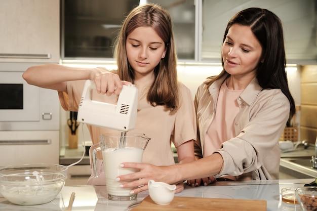 Милая девочка-подросток держит электрический миксер или блендер в большом стеклянном кувшине со свежим молоком и фруктами, готовя домашнее мороженое с мамой