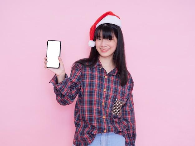 분홍색 벽에 빈 화면으로 스마트 폰 들고 산타 모자에 귀여운 십 대 소녀. 텍스트를위한 공간