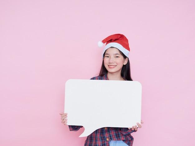Милая девочка-подросток в новогодней шапке держит белый пустой плакат на розовом фоне