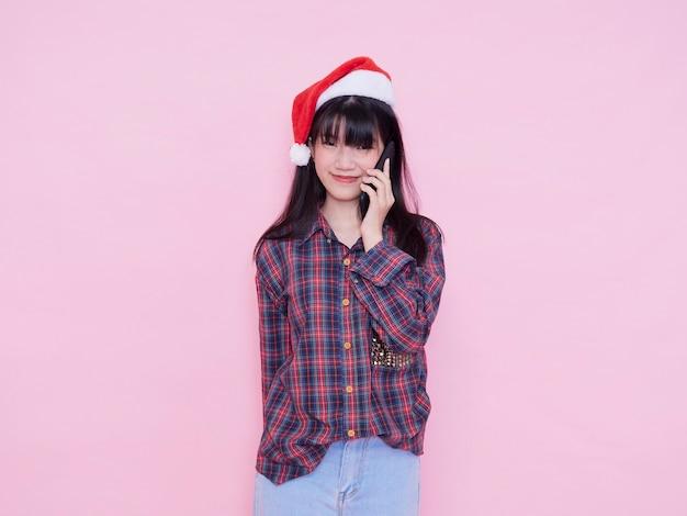Милая девочка-подросток в шляпе санты со смартфоном на розовой стене. место для текста