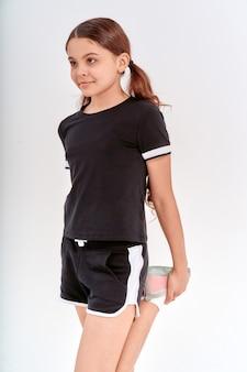 격리 된 서있는 동안 훈련하기 전에 그녀의 다리를 스트레칭 운동복에 귀여운 10 대 소녀