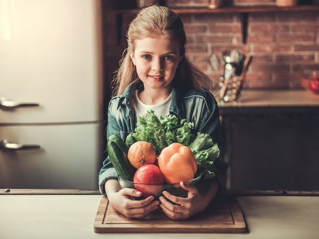 Cute teenage girl is holding a bowl with vegetables.