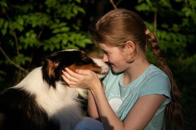 귀여운 10대 소녀가 호주 셰퍼드 강아지에게 키스합니다. 애완 동물 관리 개념입니다.