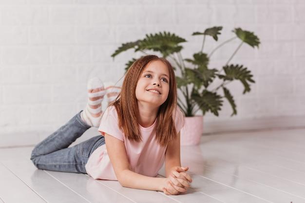 Милая девочка-подросток лежит на полу в белой комнате и мечтает