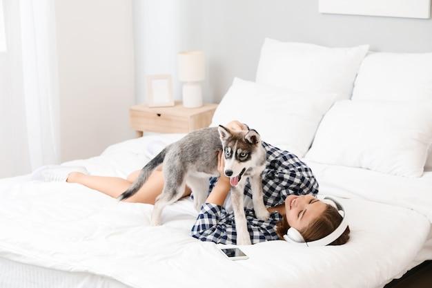 집에서 침대에 재미있는 허스키 강아지와 함께 음악을 듣고 귀여운 십 대 소녀