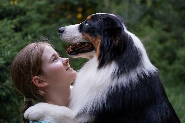 귀여운 10대 소녀가 호주 양치기 개를 쳐다봅니다. 애완 동물 관리 개념입니다. 사랑과 우정