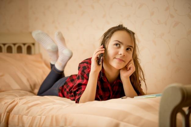 寝室に横たわって電話で話しているかわいい10代の少女