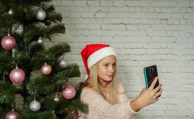 Cute teenage girl in santa hat making selfie by christmas tree at home