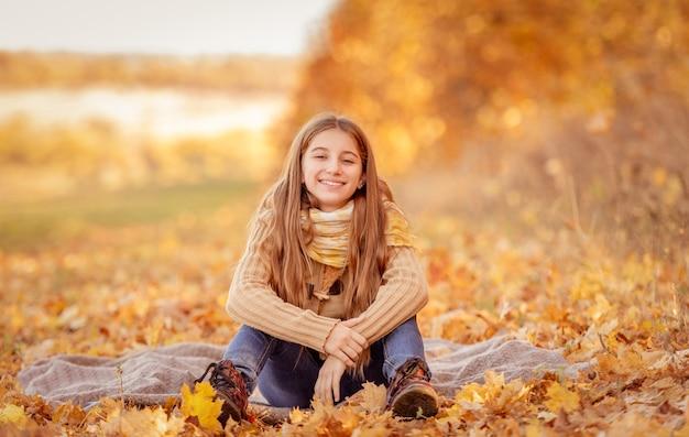 Милая девочка-подросток сидит в желтых листьях с чашкой чая