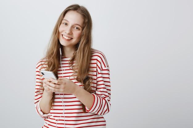 携帯電話を使用して、イヤホンで音楽を聴くかわいい十代の少女