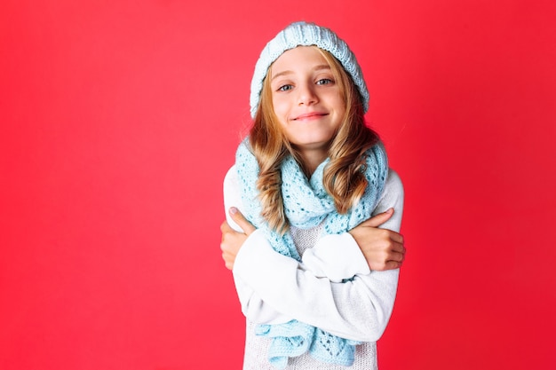 Cute teenage girl in white sweater standing isolated on red wall