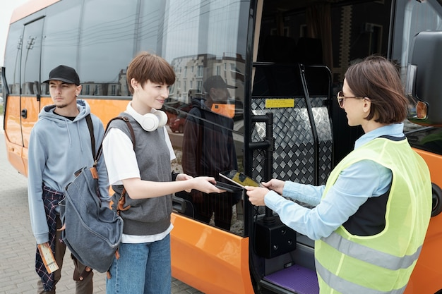 Милая девочка-подросток с рюкзаком, проверяя ее онлайн-билет