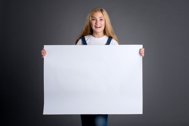 Милая девочка-подросток с длинными светлыми волосами держит белый пустой плакат на сером фоне.