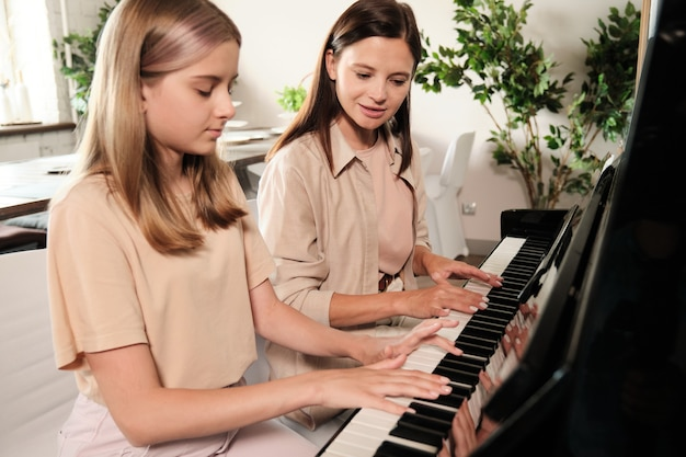 Cute teenage girl with long blond hair sitting by piano next to her mother while both playing musical stuff in living-room environment
