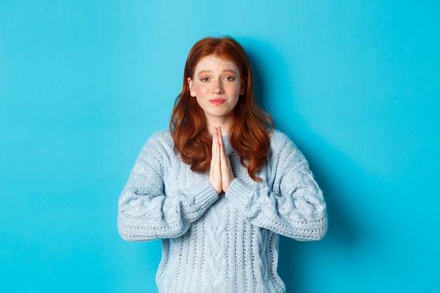 Carina ragazza dai capelli rossi che chiede aiuto, sorride mentre implora favore, ha bisogno di qualcosa, in piedi su sfondo blu