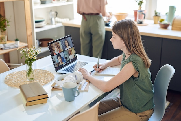 Cute teenage schoolgirl looking at teacher and several classmates on laptop display during online lesson in communication platform